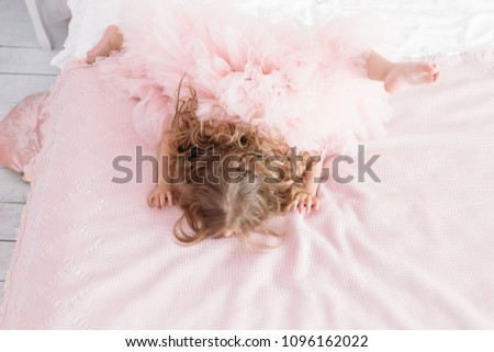 little princess lying in bed in a pink dress #1096162022