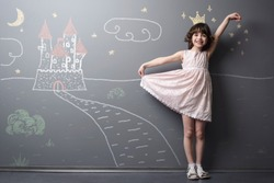 Little princess near her castle smiles and holds her dress with hand. Depicted road, crown and stars on the neutral background. True emotion of happiness of the child.