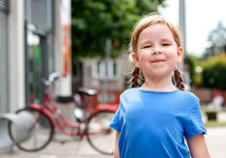 Little proud girl, child standing looking at the camera with chin up, holding head up high, smug face, back straight. Sassy proud pose and expression young kid portrait, closeup, outdoors lifestyle