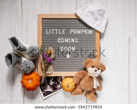 Little pumpkin coming soon sign. Baby announcement sign on a rustic white background. Coming soon concept.  Autumn pregnancy.