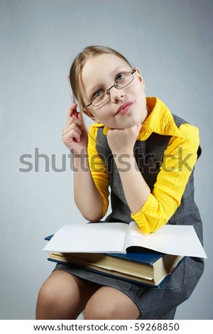 Little pupil girl with book. Sitting and writing