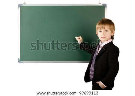 little pupil writes with chalk  on blackboard
