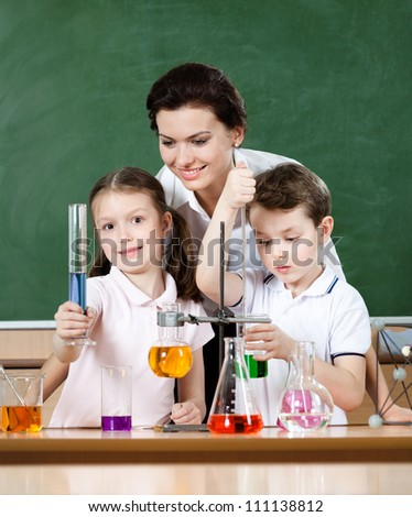 Little pupils study chemistry with their teacher at laboratory class