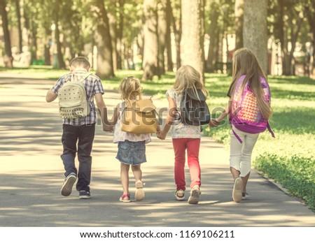 Little pupils walking home from school across the sunshine park #1169106211