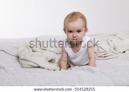 Little rascal toddler girl playing on the bed in the nursery