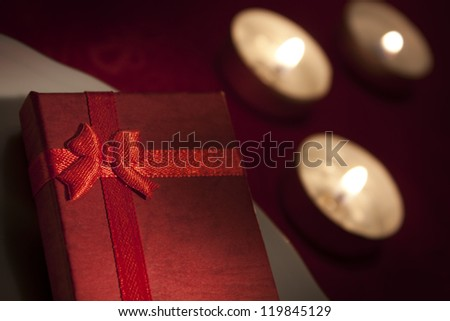 Little red gift on the table with candles