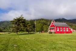 little red school house in a green meadow of northern California