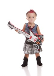 Little Rock Star.  Adorable toddler dressed as a rock star and playing with a toy guitar.  Isolated on white.