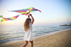 Little running girl with flying kite on tropical beach at sunset