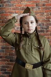 Little sad girl in military uniform at the May 9 celebration in Russia, Victory Day.