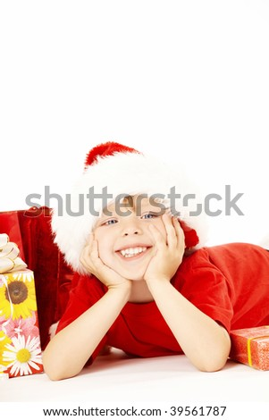 Little santa lies near to the gift boxes, isolated