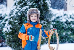 Little school boy having fun with sleigh ride during snowfall. Hapy child sledding on snow. Preschool kid riding a sledge. Child playing outdoors in snowy winter park catching snowflake.