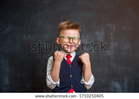 Photo of  Little school boy so happy and luck. Back to school. Kid isolated on chalkboard.