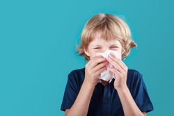 Little school boy with blonde hair sneezing to handkerchief and having runny nose. Flue, cold, allergy and disease concept