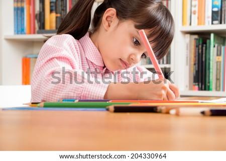 Little school girl wearing an overall doing homework
