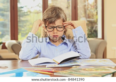 Little schoolboy bored of doing his homework at home