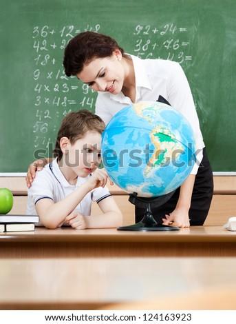 Little schoolboy studies geography with terrestrial globe