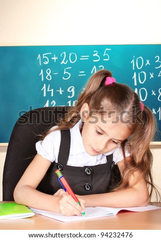 little schoolchild in classroom near blackboard