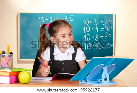 little schoolchild in classroom near blackboard