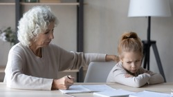 Little schoolgirl feel unmotivated to do prepare homework with mature grandmother, caring grandparent studying with ill-behaved naughty small girl child at home, education, school problem concept