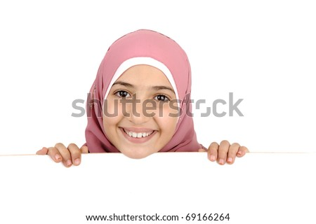 Little schoolgirl holding a blank white sign for your message. Good for borders of articles or websites. Beautiful arabic muslim model. Isolated on white background.