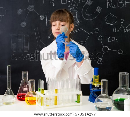 little schoolgirl in white gown looking through magnifier on reagents in chemistry lab