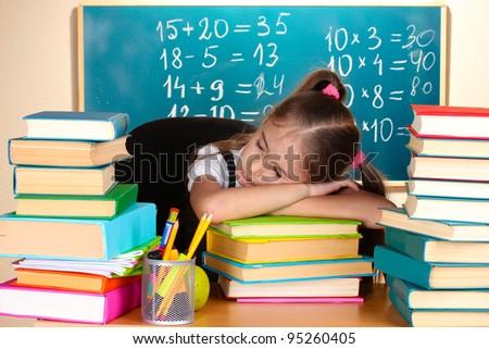 little schoolgirl sleep in classroom near blackboard