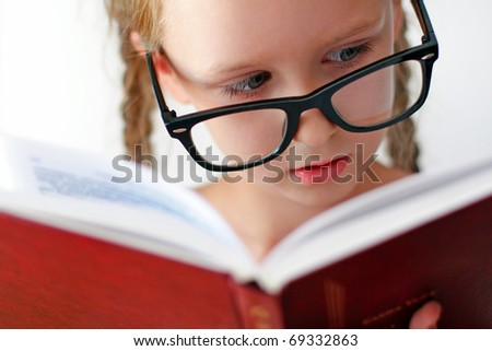 Little schoolgirl with books. Studio shot
