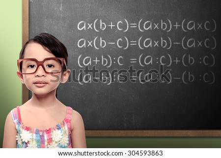 little schoolgirl with green chalkboard with math formulas