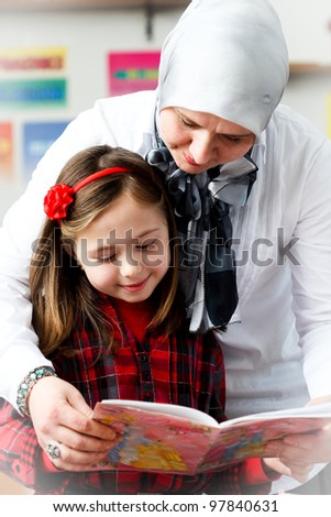 little schoolgirl with her young teacher in the classroom
