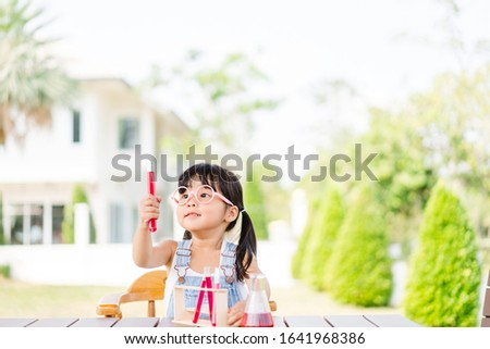 Little scientist asian toddler nerd girl wearing glasses with red liquid into flask and shaking.Home school girl learning about science and pouring reagent into flask.Chemistry class at home.Nerd kid.