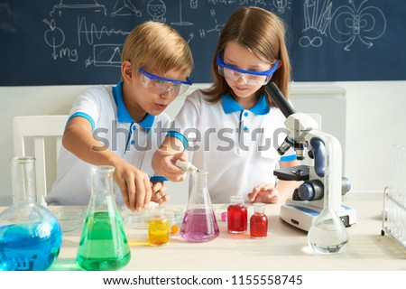 Little scientists adding color dye into beakers