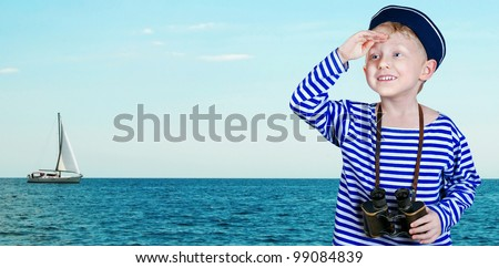 Little ship boy with binoculars looks into the distance from the arm at the sea view