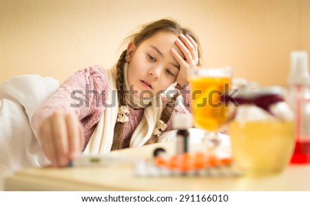 Little sick girl lying in bed and taking thermometer from bedside table
