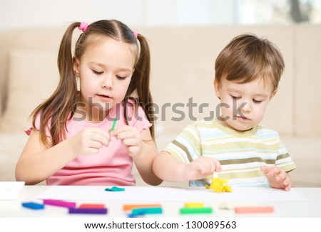 Little sister and brother are playing with plasticine - stock photo