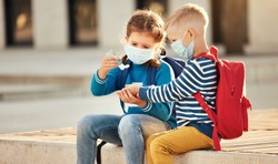 Little sister and brother in protective masks with school backpacks disinfecting hands with sanitizer while sitting on street