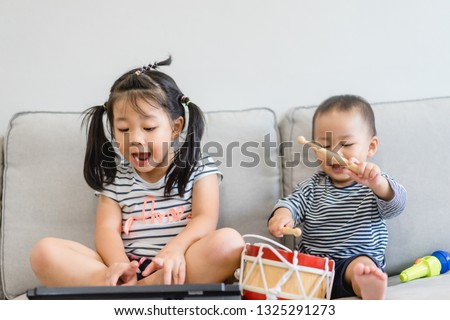 Little sister and her baby brother play with keyboard and drum and singing.Asian child playing and singing happy moment in music time.Sibling child sing in music song class at home.