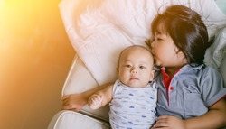 Little sister hugging and kissing her brother.Toddler kid meeting new sibling. Cute girl and baby boy relax in a white bedroom.Family with children at home. Love, trust and tenderness