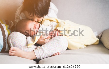 Little sister hugging and kissing her newborn brother.Toddler kid meeting new sibling. Cute girl and new born baby boy relax in a white bedroom.Family with children at home. Love, trust and tenderness #612626990