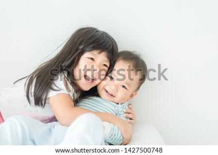 Little sister hugging her baby brother in the morning.Toddler kid meeting new sibling.Cute girl and baby boy relax at home in Japan.Family with children at home. Social distancing covid-19 coronavirus Foto stock ©