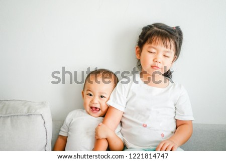 Little sister hugging her baby brother.Toddler kid meeting new sibling. Cute girl and baby boy relax at home in Japan.Family with children at home. Love, trust and tenderness. Foto d'archivio ©