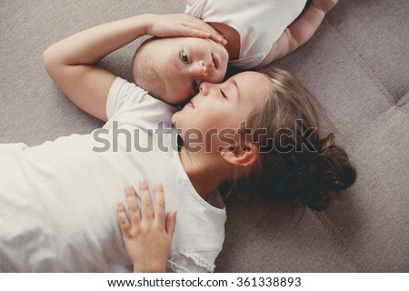 Little sister hugging her newborn brother. Toddler kid meeting new sibling. Cute girl and new born baby boy relax in a white bedroom. Family with children at home. Love, trust and tenderness