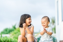 Little sister playing with her baby brother.Toddler kid meeting new sibling. Cute girl and baby boy clapping hands at home in Japan.Family with children at home. Love, trust and tenderness.