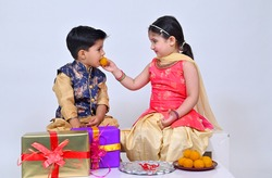 Little sister Tieing rakhi to little brother on the occasion of  Raksha Bandhan and putting ladoo in her brother mouth  as part of the rituals