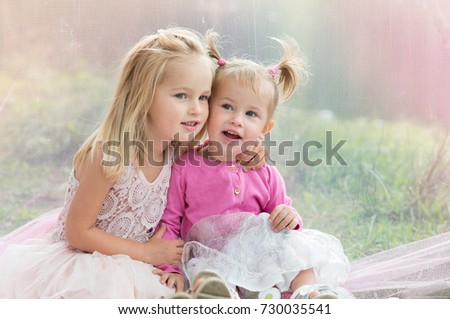 Little sisters: girls having fun in the summer forest, sitting on the blanket and smiling