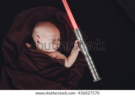 Stock Photo Little Sleeping Cute Newborn Baby with Laser Beam In Brown Mantle Cape. Isolated On Black Background