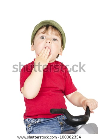 Little sleepy boy on a plastic toy motorcycle. Isolated on white.