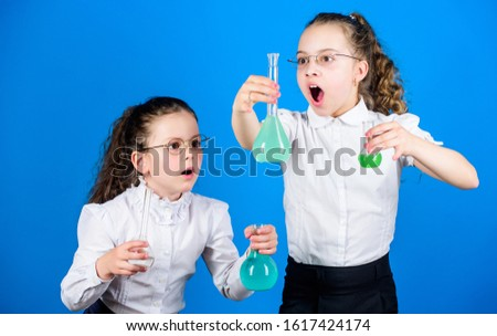 little smart girls with testing flask. back to school. school kid scientist studying science. biology education. children study chemistry lab, discovery. discovery concept. discover new element.