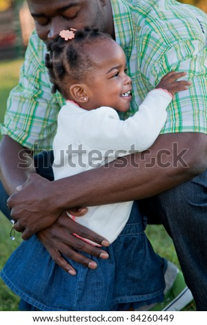 Little Smiling African American Girl Hugging Dad Outdoor
