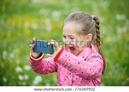 Little smiling and curious girl photographing with her smart phone, exploring nature and standing in a dandelion meadow. Active lifestyle, curiosity, pursuing a hobby, technology and kids concept.